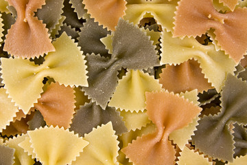close up of uncooked multi-colored bow pasta