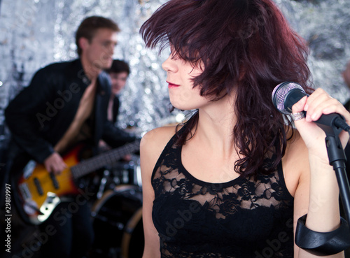 Beautiful rock singer with her band in the background