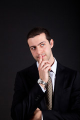 Thoughtful young businessman isolated on black
