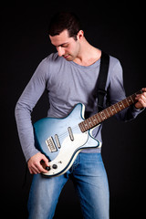 Young man playing guitar isolated on black