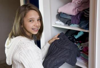 jeune adolescente qui range ses habits dans son placard