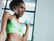 african woman exercising with small weights in gym