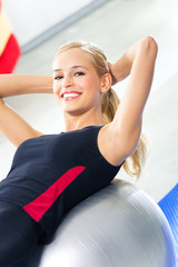 Young smiling woman in sportswear working out with fit ball