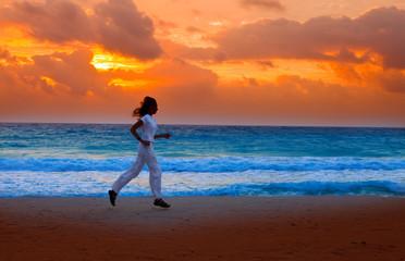 Silhouette of woman,running on sunset along ocean coast