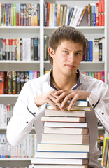 Young man sitting with books in the library