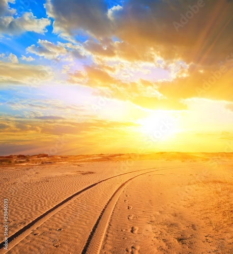 road in a sand desert at the sunset