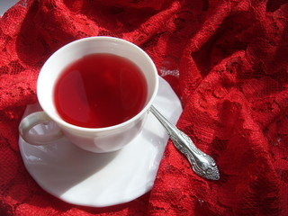 Cup with juice and saurce with a spoon on a red guipure.