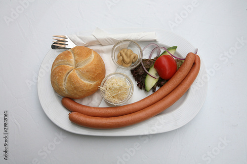 Vienna sausages with bread and salad on a white background