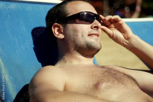 Young handsome man lying on blue sunbed and taking sunbath