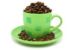 green cup with coffee beans over a white background
