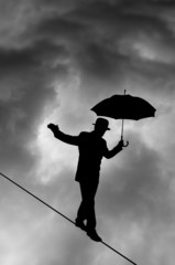 Tightrope Silhouette against black cloud