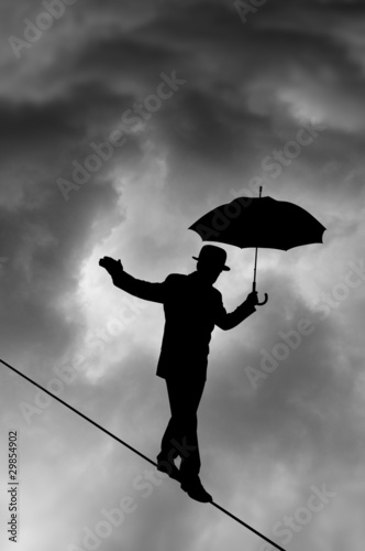 Tightrope Silhouette against black cloud