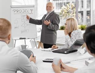 Senior businessman talking to colleagues