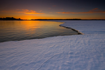 Sunset reflection and snowy ice.