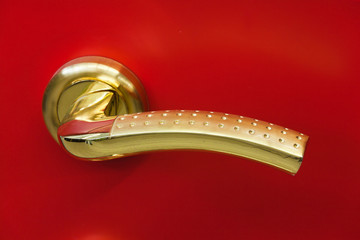 golden door handle on a red background