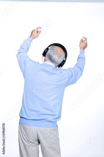 Back of a senior man listening to the music;