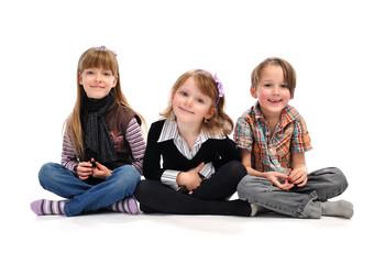 3 Kinder sitzen im Schneidersitz auf dem Boden