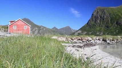 Red wooden house near sandy beach
