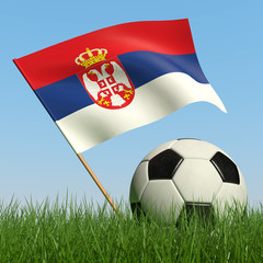 Soccer ball in the grass and flag of Serbia.