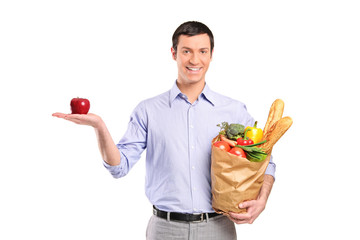 Smiling man holding a red apple and a grocery bag