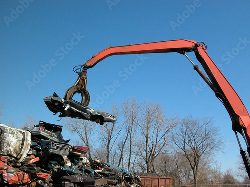 junkyard crane and claw with crushed car