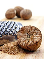 Selection of nutmeg with grater on a wooden background