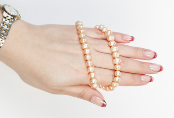 The female hand with beautiful manicure holds pearls thread