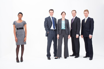 Businesswoman standing apart from four smiling businesspeople