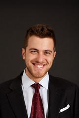 Handsome smiling businessman on dark background