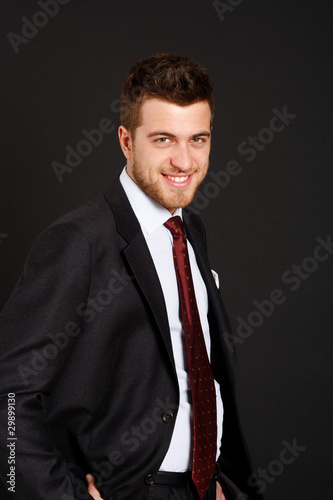 Young smiling businessman on dark background