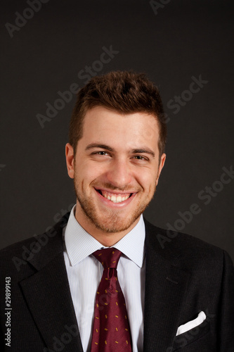 Handsome smiling businessman on dark background