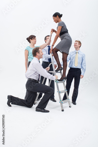 Businesspeople helping businesswoman climbing up ladder