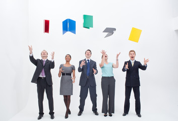 Five happy businesspeople throwing away file folders