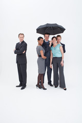 Businessman standing apart from four businesspeople with umbrella