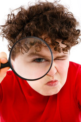 Boy looking through magnifying glass isolated on white