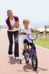 happy mom teaching daughter to ride bike