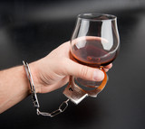 A hand locked to glass of alcohol poster