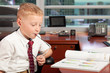 Cute young boy in a business office reading a magazine