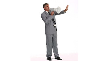 Man in gray suit speaking on a megaphone