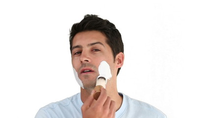 Dark-haired man putting on shave foam