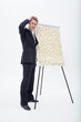 Confused businessman standing at flipchart with abundance of post-its