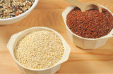 Red and white quinoa in small containers and wild rice