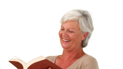 Mature woman reading a book and she is laughing
