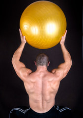 Perfect muscular man with yellow ball posing artistic