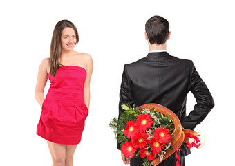 Man in black suit hiding  flowers and an attractive woman