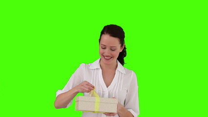 Cute brunette woman opening a gift