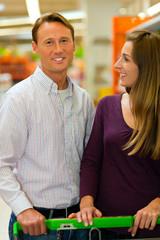 Paar im Supermarkt mit Einkaufswagen
