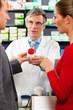Apotheker in seiner Apotheke mit Kunden