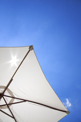 white linen umbrella in front of a deep blue sky