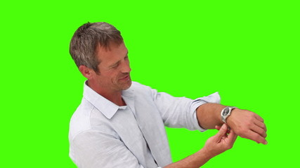 Man in shirt putting on a watch